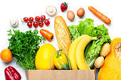 Healthy food in shopping bag. Vegetables and fruits assortment isolated on white background. Vegetarian healthy food concept.