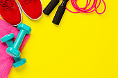 Fitness and sport concept. Red sneakers, jump rope, dumbbells and pink towel on bright yellow background. Free space