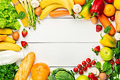 Vegetables, fruits assortment frame on white wooden background. Vegetarian healthy food concept. Food and grocery shopping. Free space