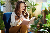 trendy woman with long wavy hair in living room in sunny day