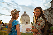 happy stylish mother and daughter with map enjoying promenade
