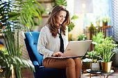 woman with long wavy hair in sunny day using laptop