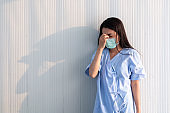 Female patient wearing mask standing by the wall feeling pain and depression. Young women recovering from surgery. Young Asian patient women in hospital. Patient with depressed and sad look by the wall.