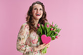 happy woman with long wavy brunette hair on pink