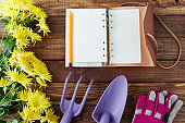 spring flat lay with notebook, gardening tools and gloves