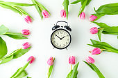 spring flat lay with tulips and alarm clock on table