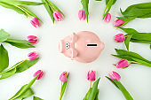 spring flat lay with piggy bank on white