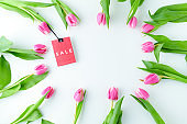 spring flat lay with sale label and tulips on white