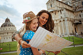 happy trendy mother and daughter exploring attractions