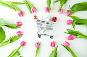 spring flat lay with gifts, tulips and shopping cart