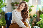 smiling trendy woman with long wavy hair in house in sunny day