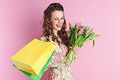 smiling trendy woman in floral dress on pink