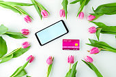 spring flat lay with credit card, tulips and smartphone