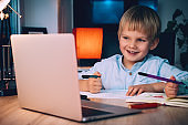 School boy with laptop at table in evening at home. Child using digital technology and internet communication.