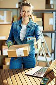 smiling modern woman in jeans with parcels in warehouse