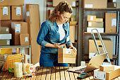 modern female in jeans using smartphone app in warehouse
