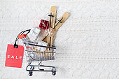 winter flat lay with sale tag, presents and shopping cart