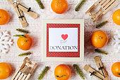winter flat lay with donation box, snowflakes and mandarins