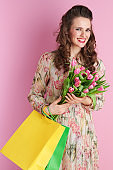happy elegant female with long wavy brunette hair on pink