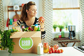 happy woman with food box in kitchen