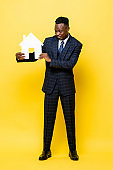 Young African businessman as a real estate agent holding house cutout model in yellow isolated studio background