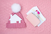 winter flat lay with utility bills, paper house and hat