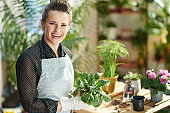 smiling woman in rubber gloves in sunny day do gardening