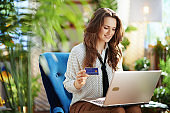 smiling elegant woman in sunny day using laptop