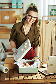 business owner woman in office packing product for delivery