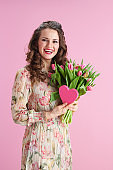 happy stylish female with long wavy brunette hair on pink