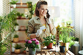 smiling woman in rubber gloves in sunny day using phone