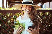 smiling stylish woman sending text message using phone