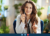 smiling woman with long wavy hair in sunny day using video chat