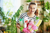 happy housewife in striped shirt in living room in sunny day