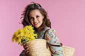 Portrait of smiling elegant woman in floral dress on pink