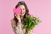 happy stylish woman in floral dress on pink