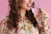 Smiling woman with long wavy brunette hair on pink