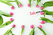 spring flat lay with sale label and tulips on table