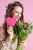 smiling elegant woman in floral dress on pink