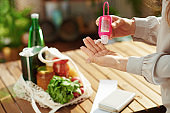 Female in kitchen disinfecting hands after grocery shopping
