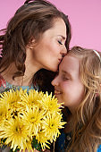 smiling stylish mother and daughter hugging and kissing on pink