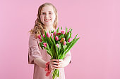 happy stylish child in pink dress on pink
