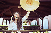 happy modern female in white shirt talking on smartphone