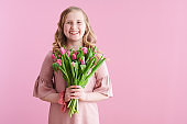 happy stylish girl in pink dress on pink