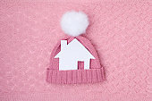 winter flat lay with paper house and hat with pompom