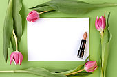 spring flat lay with lipstick isolated on green