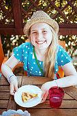 smiling trendy girl sitting at table having brunch