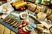 desk with electric grill, grilled sausages, bread and camembert