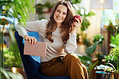 smiling woman with long wavy hair in house in sunny day
