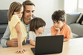 Happy dad sitting at table, embracing kids and using laptop